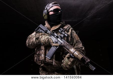 Man in uniformmask and in dark glasses with rifle on dark wall background