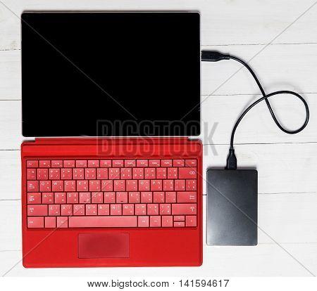 USB External hard disk on Red tablet computer keyboard