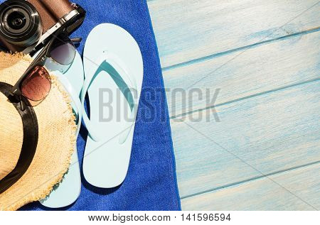 beach accessories. stylish sunglasses with flip flops, camera, hat and towel on blue wooden table