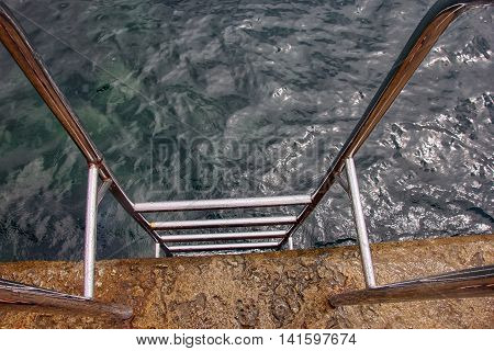 swimming ladder stainless steel for descent into water on concrete pier on Black sea in Crimea