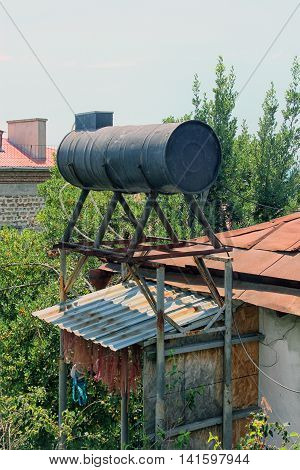 big black metal round water tank on th roof of house in Crimea