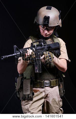 Girl with rifle in bulletproof vest and helmet on dark background