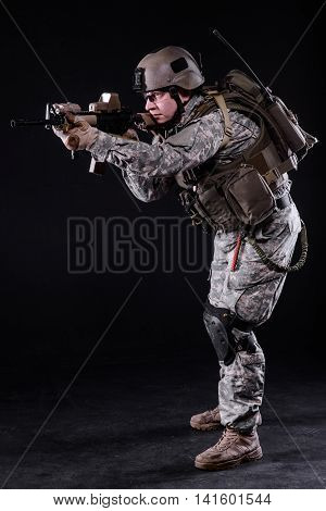 Soldier in bulletproof vest and helmet aiming from rifle on dark background