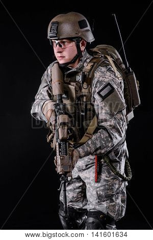 US special forces soldier in helmet with gun on dark background