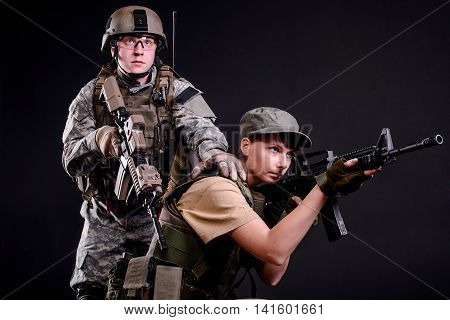 Man and woman in military uniform with guns on dark background