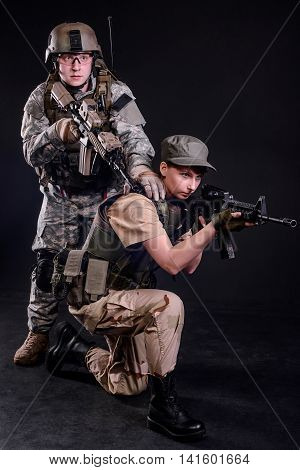 Military Couple In Uniform with guns on dark background