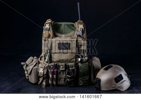 Bulletproof vesthelmet and other military equipment on black background