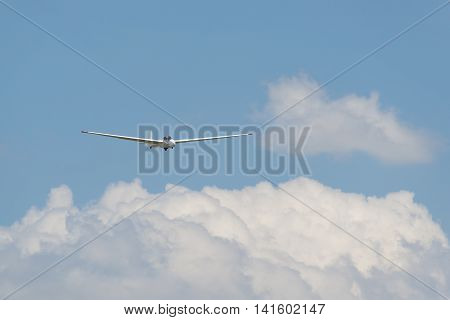 Glider above white clouds against a blue sky as background picture for extreme sports