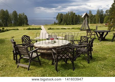 Eight chairs round a round table of stone on a green lawn with a sea in background picture from the North of Sweden.
