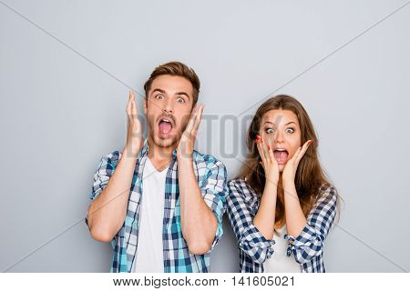 Portrait Of Shocked Man And Woman Screaming And Touching Face