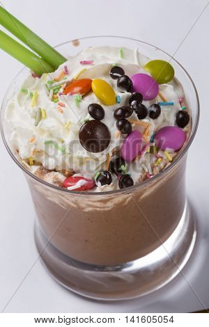 Chocolate and coffee latte beverages with whipped cream. Colorful candy and confections added on the cocktail.