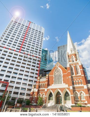 Contrasting arctitecural styles modern commercial skyscrapers surround traditional Albert Street Uniting church in Brisbane city Australia