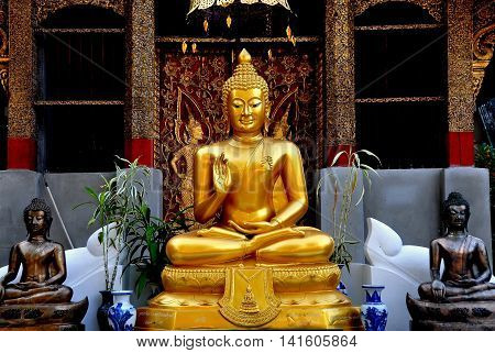 Chiang Mai Thailand - December 18 2012: Gilded Buddha statue seated in the lotus position with uplifted hand at Wat Sum Pao
