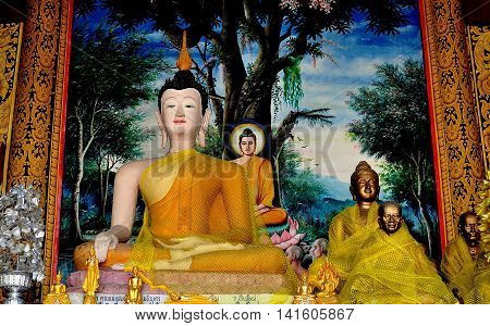 Chiang Mai Thailand - December 26 2012: Statue of seated Buddha with devoted Monks wrapped in yellow robes at Wat Chedi Liem