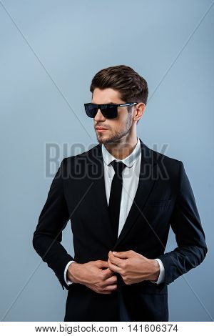 Successful Businessman In Black Glasses Buttoning His Suit