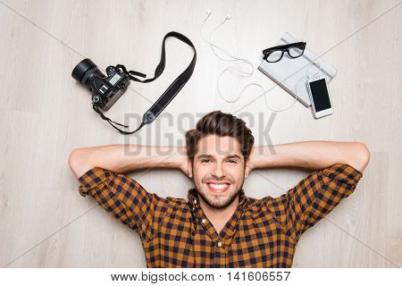 Top View Of Cheerful Happy Man Lying On Floor With Camera, Glasses And Smartphone