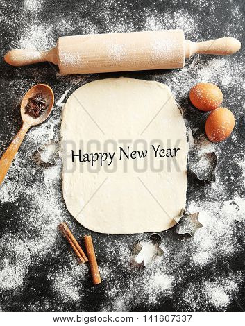 Rolling pin with spoon eggs and flour on wooden black table, happy new year