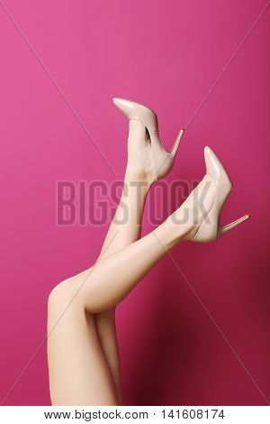 Female Legs With Beige High Heels On A Grey Background