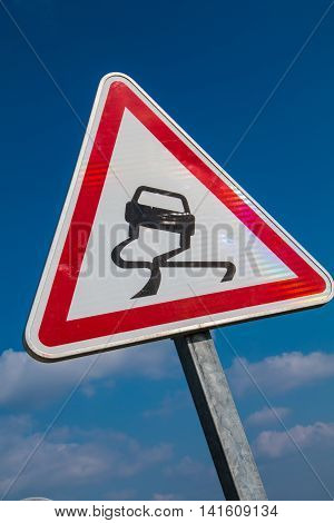 Slippery Road Warning Sign on blue sky