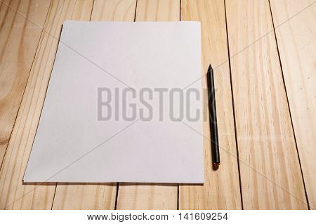 White blank paper with pencil on wooden texture background low key tone