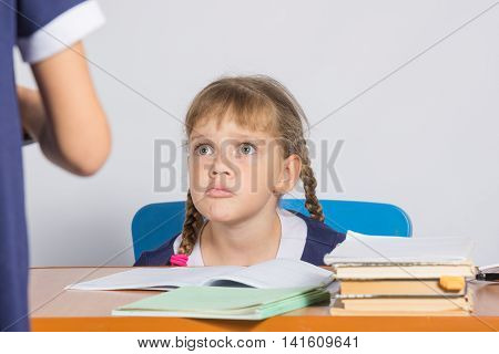 Schoolgirl Sitting At The Desk Angrily Looks At Another Girl
