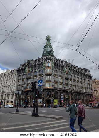 SAINT PETERSBURG, RUSSIA, MAY 27, 2014: a front view of the Zinger building from across the street, with pedestrians, and electrical wires overhead, in the early afternoon, on a cloudy day