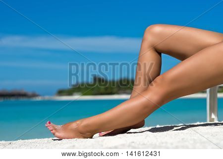 Young woman sunbathing on beach lounger. Legs.