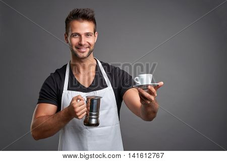 A young barista man smiling and holding a percolator and offering a cup of coffee