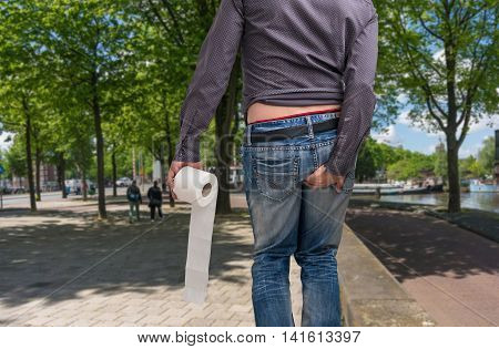 Man Has Diarrhea. Man Holding Toilet Paper And Butt.