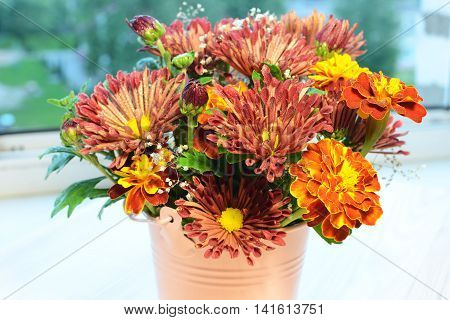 Bouquet of autumn flowers on the window sill at home