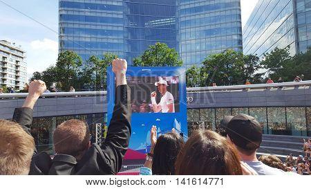 London, England - July 10, 2016 Crowd watching Wimbledon men's final tennis match on big screen at London Bridge City Summer Festival