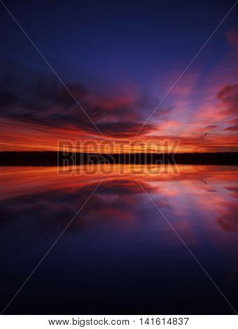 Beautiful crimson sunset over a mountain lake.