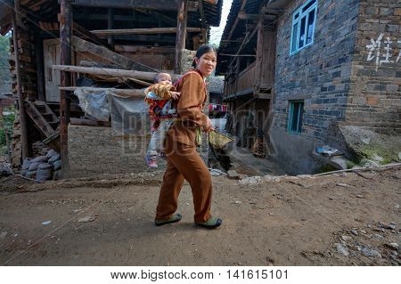Zhaoxing Dong Village Guizhou Province China - April 9 2010: Chinese woman walking on a dirt road rural street carries the baby on her back.