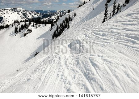 Steep run in an alpine ski area with tracks in the snow