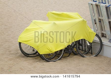 Bicycles on the beach covered with protective mantle