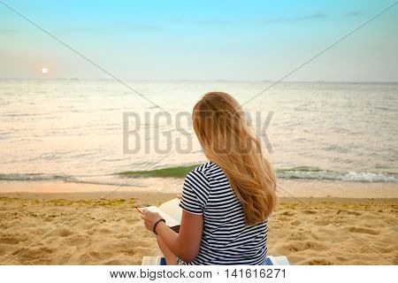 Woman reading book relaxed in deck chair