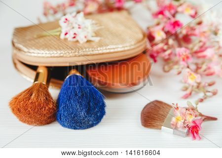 There White and Pink  Branches of Chestnut Tree,Bronze Powder;Two Make Up Brown and Blue Brushes in the Golden Cosmetic Bag are on White Table,Selective Focus