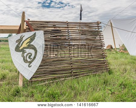 Red knight's shield with family coat of arms on grass on the nature.