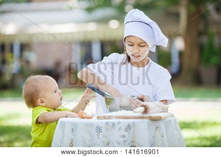 Little chef making dough, toddler boy trying to help her