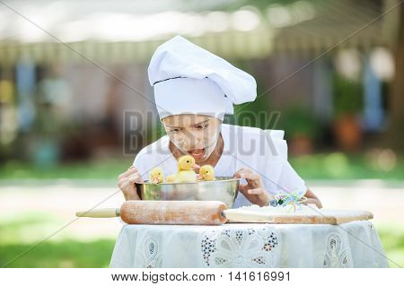 Shocked little chef showing ducklings in a bowl while cooking outdoors