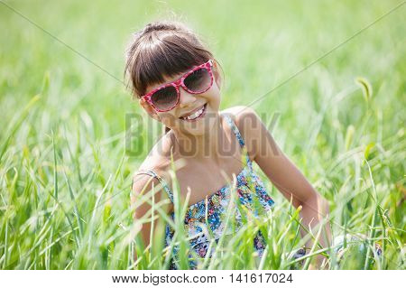 Cheerful young girl sitting on green grass in sunglasses