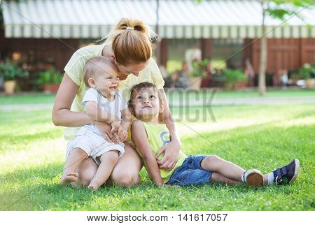 Young mother and two sons enjoying beautiful day in park