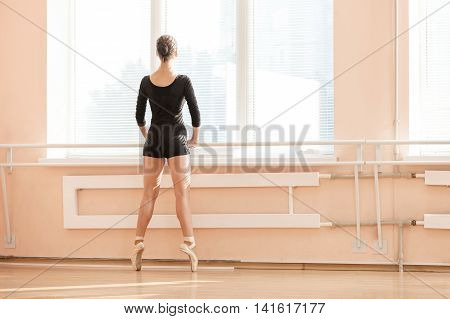 Young ballerina standing on poite at barre in ballet class