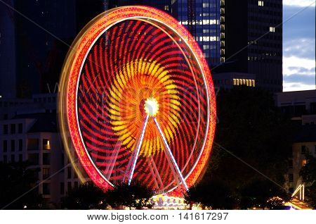 Frankfurt, Germany - August 05: Ferris wheel and rides in Frankfurt's mainfest in 2016