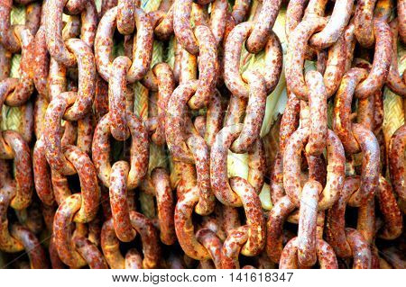 Old rusty slavery chains used for bondage displayed outside.