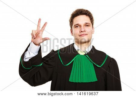 Young lawyer wear polish toga and show hand sign. Man make gesture hold three fingers in air.