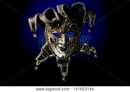 Beautiful venetian souvenir mask on black background with blue light