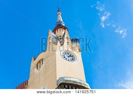 Low angle view of pointy church tower with various architectural decorations under blue sky