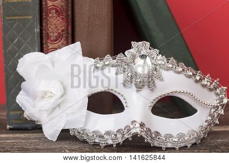 Art concept. Closeup of white classical carnival mask with vintage books and red background.