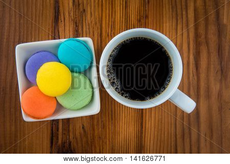 Overhead view of macaroons and coffee on wood